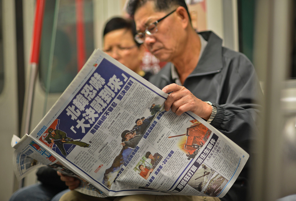 """. A man sitting on the underground in Hong Kong reads a Chinese language newspaper leading with reports on the recent North Korean military developments on March 31, 2013.  North Korea on March 30 declared it was in a \""""state of war\"""" with South Korea and warned Seoul and Washington that any provocation would swiftly escalate into an all-out nuclear conflict. China, North Korea\'s sole major ally and biggest trading partner, appealed for \""""joint efforts\"""" to reduce tensions on the Korean peninsula on March 29.     AFP PHOTO / Antony DICKSON        (Photo credit should read ANTONY DICKSON/AFP/Getty Images)"""