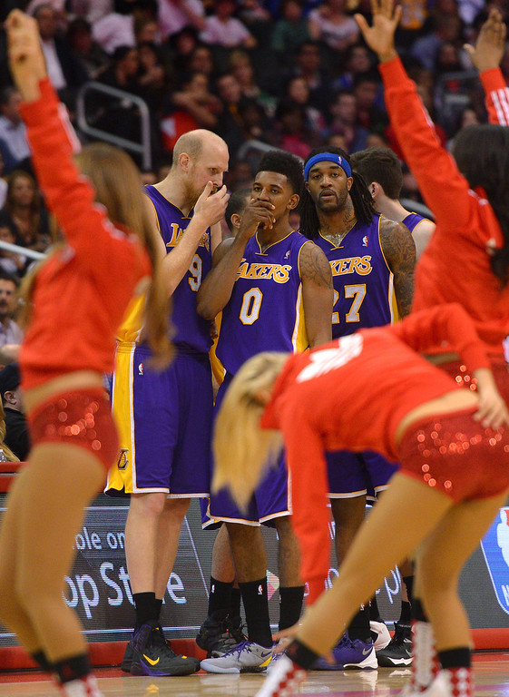 . Lakers reserves strategize as the Clippers Spirit performs during a timeout. (Photo by Michael Owen Baker/L.A. Daily News)