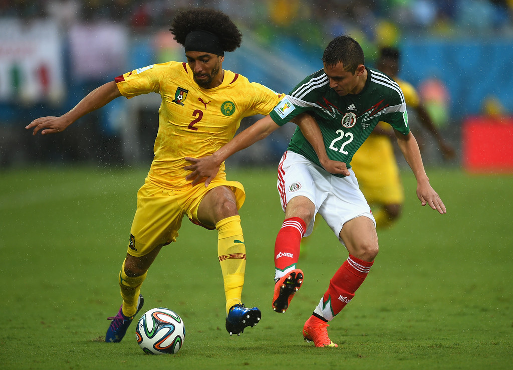 . Benoit Assou-Ekotto of Cameroon holds off Paul Aguilar of Mexico in the first half during the 2014 FIFA World Cup Brazil Group A match between Mexico and Cameroon at Estadio das Dunas on June 13, 2014 in Natal, Brazil.  (Photo by Matthias Hangst/Getty Images)