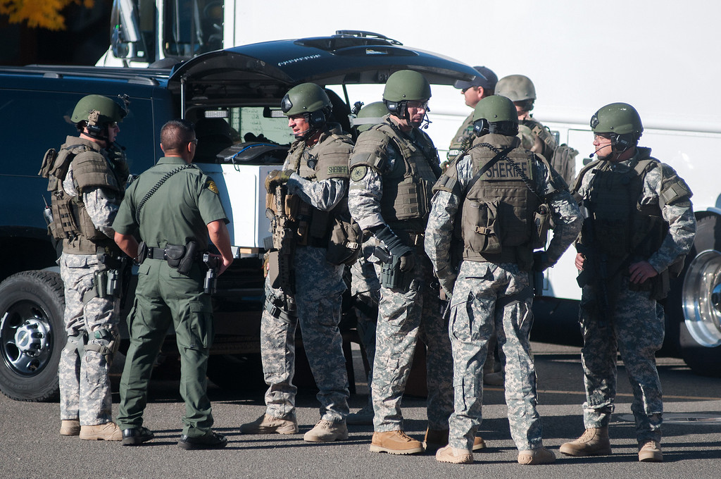 . Swat team members secure the scene near Sparks Middle School in Sparks, Nev., after a shooting there on Monday, Oct. 21, 2013.  Authorities are reporting that two people were killed and two wounded at the Nevada middle school. (AP Photo/Kevin Clifford)