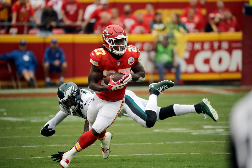 . Kansas City Chiefs running back Kareem Hunt (27) runs past a tackle attempt by Philadelphia Eagles safety Malcolm Jenkins, rear, during the first half of an NFL football game in Kansas City, Mo., Sunday, Sept. 17, 2017. (AP Photo/Charlie Riedel)