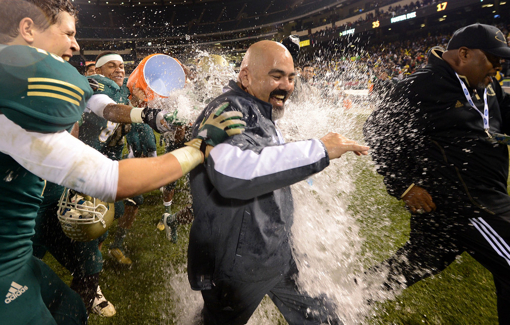 . Anaheim, Calif., --12-01-12 - Long Beach Poly\' head coach  Raul Lara has water dumped on him after he and his team defeated Mater Dei 35-17 for the CIF-SS Pac-5 Division championship, at Anaheim Stadium.   Stephen Carr/  LANG