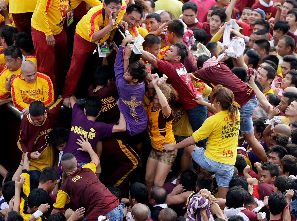 . Catholic devotees, including women, jostle to get closer to kiss the rear end of the cross of the centuries-old image of the Black Nazarene in a raucous celebration on its feast day Wednesday, Jan. 9, 2013 in Manila, Philippines. The annual procession by hundreds of thousands of devotees is now becoming to be a tourist attraction.  More than a hundred devotees were treated for mostly minor injuries. (AP Photo/Bullit Marquez)