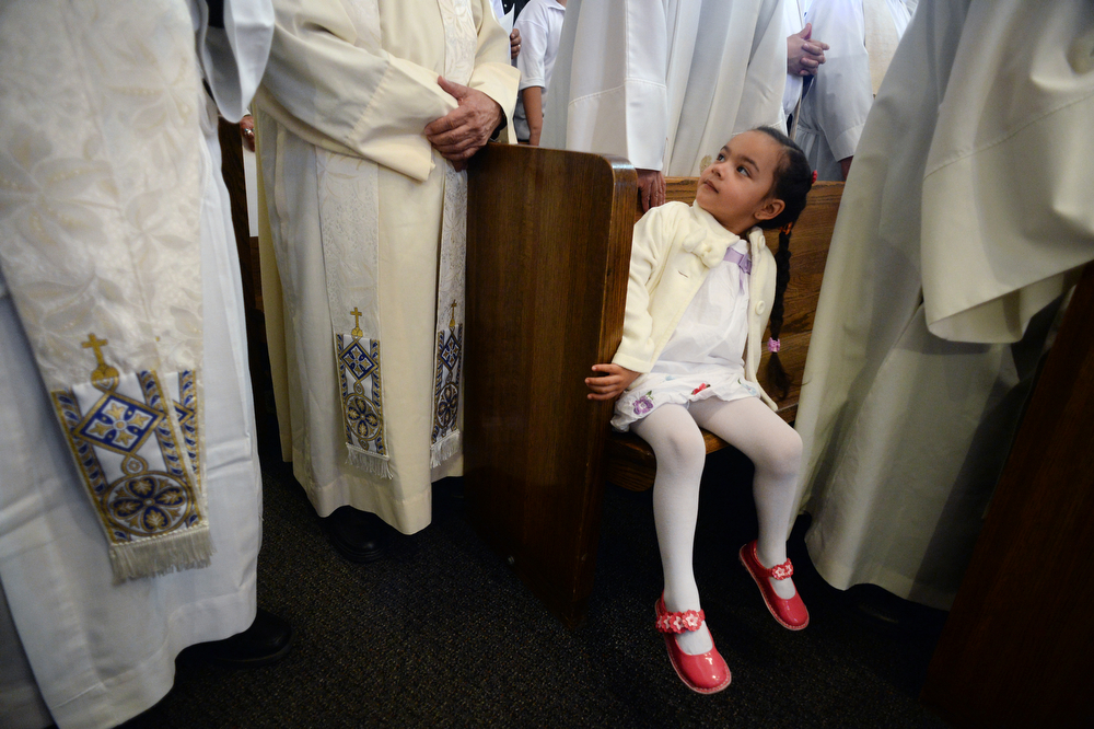 . A young girl is surrounded by Theatine fathers during the funeral services held for Father Tomas Fraile at St. Cajetan Church at 299 South Raleigh St. in Denver, Co on March 26, 2014.  Hundreds of people turned out to pay their last respects for the popular father.  (Photo By Helen H. Richardson/ The Denver Post)