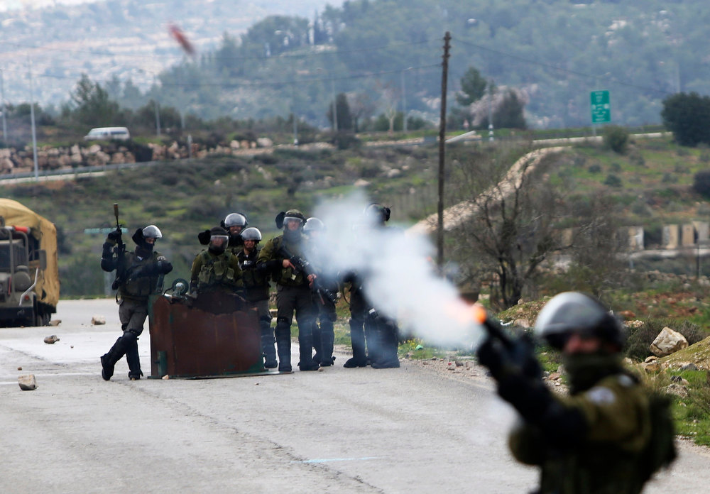 Description of . An Israeli security officer fires a tear gas canister during clashes with stone-throwing Palestinians (not pictured) at a weekly protest against Jewish settlements, in the West Bank village of Nabi Saleh, near Ramallah February 1, 2013. U.N. human rights investigators called on Israel on Thursday to halt settlement expansion and withdraw all half a million Jewish settlers from the occupied West Bank, saying that its practices could be subject to prosecution as possible war crimes. REUTERS/Mohamad Torokman