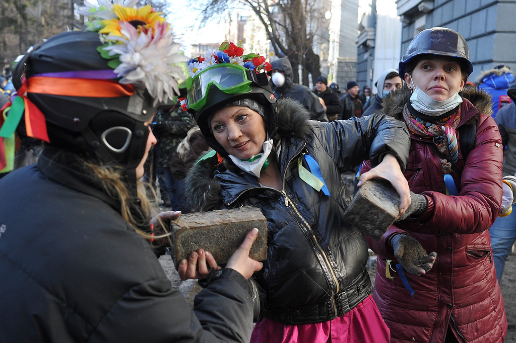 . Women pass stones to protesters during an anti-government protest in downtown Kiev, Ukraine, 18 February 2014. A least three protesters were killed in clashes with police on 18 February, Ukrainian opposition activists say.   EPA/ALEXEY FURMAN