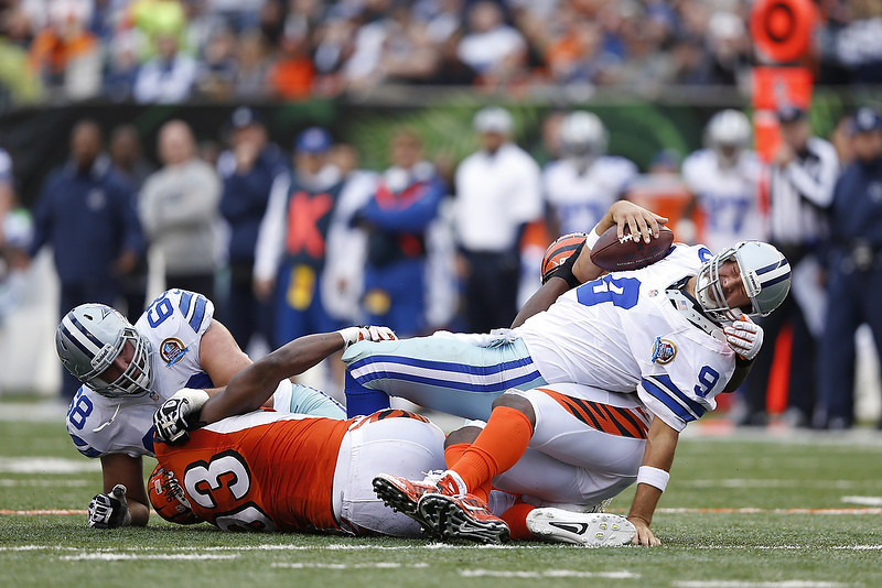 . Michael Johnson #93 and Carlos Dunlap #96 of the Cincinnati Bengals combine to sack Tony Romo #9 of the Dallas Cowboys during the game at Paul Brown Stadium on December 9, 2012 in Cincinnati, Ohio. (Photo by Joe Robbins/Getty Images)