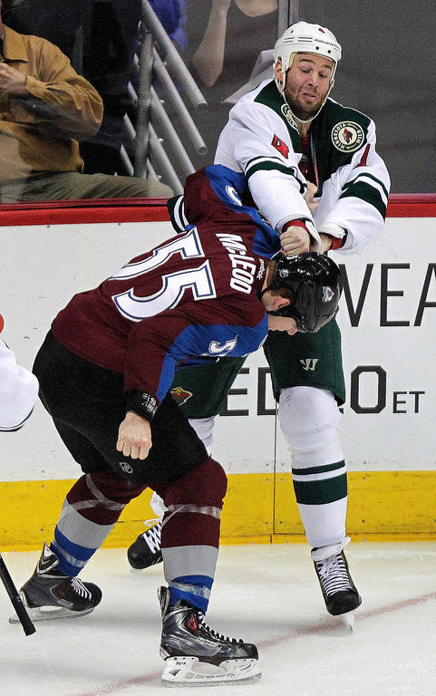 . Minnesota Wild\'s Clayton Stoner, top, takes a swing at Colorado Avalanche\'s Cody McLeod, bottom, during the first period of an NHL hockey game Thursday, Jan. 30, 2014, in Denver. (AP Photo/Barry Gutierrez)