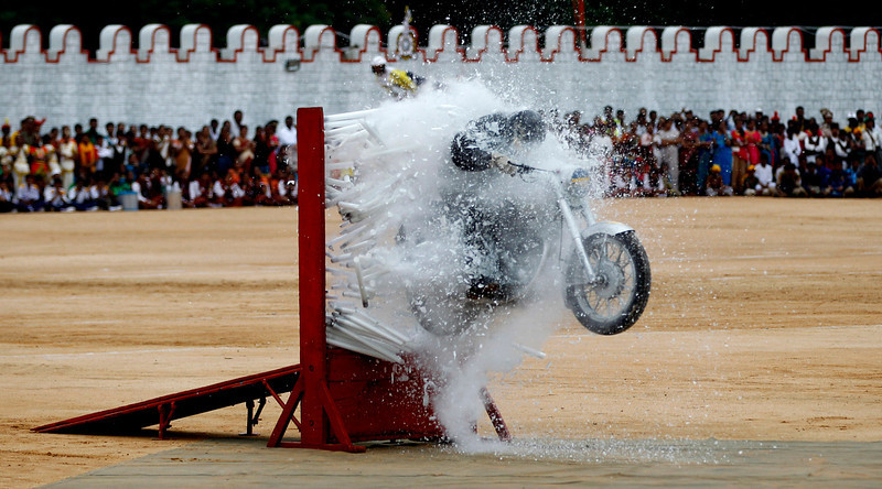 . An Indian army officer performs a stunt on a motorcycle during a function to mark India\'s Independence Day in Bangalore, India, Thursday, Aug. 15, 2013. (AP Photo/Aijaz Rahi)