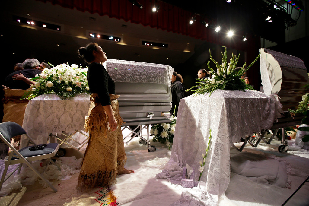 ". Hinemoa Garcia, front, stands by the caskets of her nephews Polo Manukainiu, right, a Texas A&M redshirt freshman, and Andrew ""Lolo\"" Uhatafe, left, during a memorial service at Trinity High School, Friday, Aug. 9, 2013, in Euless, Texas. More than 2,500 people showed up to mourn the two who were killed in a single car accident in New Mexico, on July 29. Also killed in the accident was 18-year-old Utah recruit Gaius \""Keio\"" Vaenuku. (AP Photo/Tony Gutierrez)"
