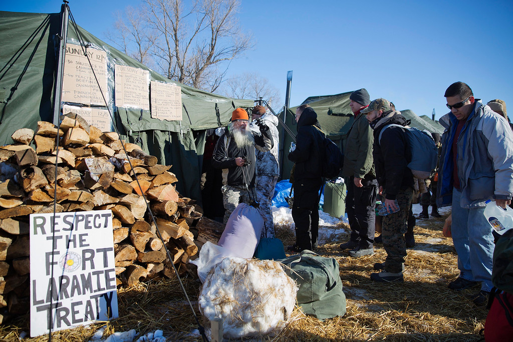 . Veterans line up after arriving at the Oceti Sakowin camp where people have gathered to protest the Dakota Access oil pipeline in Cannon Ball, N.D., Sunday, Dec. 4, 2016. Tribal elders have asked the military veterans joining the large Dakota Access pipeline protest encampment not to have confrontations with law enforcement officials, an organizer with Veterans Stand for Standing Rock said Sunday, adding the group is there to help out those who\'ve dug in against the four-state, $3.8 billion project. (AP Photo/David Goldman)