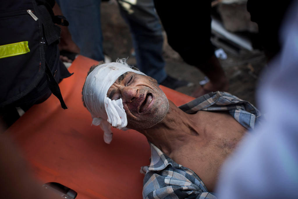 . In this Nov. 18, 2012 file photo, a member of the Abdel Aal family is rescued after his family house collapsed during an Israeli forces strike in the Tufah neighborhood, Gaza City. This photo was one in a series of images by Associated Press photographer Bernat Armangue that won the first place prize in the World Press Photo 2013 photo contest for the Spot News series category.  (AP Photo/Bernat Armangue, File)