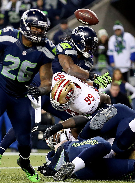 . Running back Marshawn Lynch #24 of the Seattle Seahawks is hit by outside linebacker Aldon Smith #99 of the San Francisco 49ers as the ball is loose after it was fumbled by quarterback Russell Wilson #3 of the Seahawks on fourth and goal in the fourth quarter during the 2014 NFC Championship at CenturyLink Field on January 19, 2014 in Seattle, Washington.  (Photo by Christian Petersen/Getty Images)