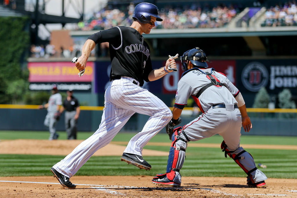 . Justin Morneau #33 of the Colorado Rockies scores a run as catcher Kurt Suzuki #8 of the Minnesota Twins waits for the throw during the first inning. (Photo by Justin Edmonds/Getty Images)