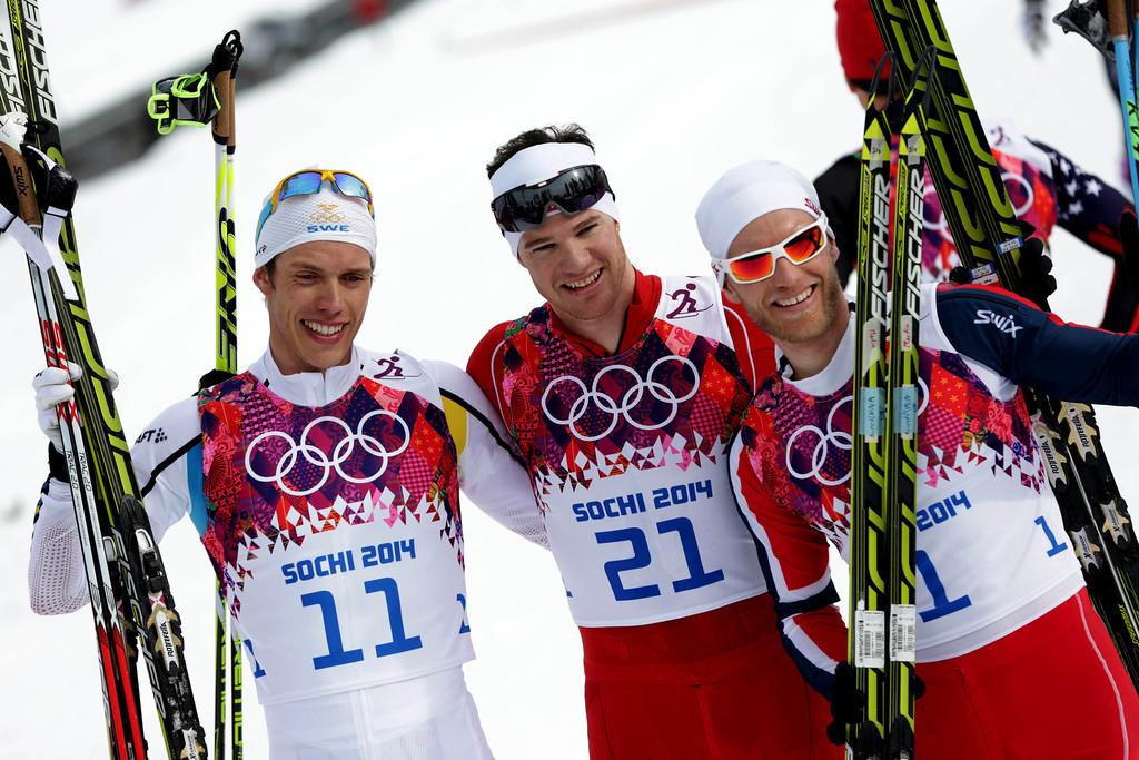 . Switzerland\'s Dario Cologna, center, winner of the men\'s cross-country 30k skiathlon, celebrates with silver medalist Sweden\'s Marcus Hellner, left, and bronze medalist Norway\'s Martin Johnsrud Sundby, at the 2014 Winter Olympics, Sunday, Feb. 9, 2014, in Krasnaya Polyana, Russia. (AP Photo/Matthias Schrader)