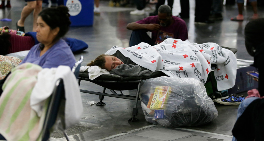 . People rest at the George R. Brown Convention Center that has been set up as a shelter for evacuees escaping the floodwaters from Tropical Storm Harvey in Houston, Texas, Tuesday, Aug. 29, 2017. (AP Photo/LM Otero)