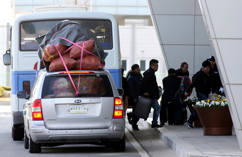 . South Korean workers who work at the Kaesong Industrial Complex in North Korea, arrive from the North by a bus, which has been used as a commuting bus to Kaesong, as a van carrying products made in Kaesong is seen at the South\'s CIQ (Customs, Immigration and Quarantine), just south of the demilitarized zone separating the two Koreas, in Paju, north of Seoul, April 9, 2013. North Korea warned foreigners in South Korea on Tuesday to quit the country because they were at risk in the event of conflict, the latest threat of war from Pyongyang.    REUTERS/Kim Tae-hyong/The Hankyoreh