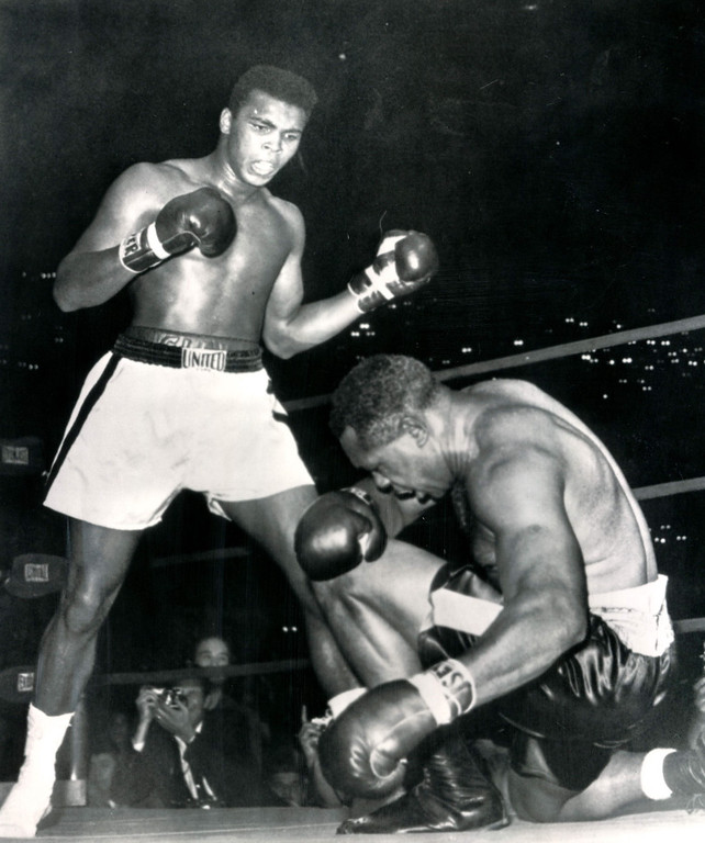 . LOS ANGELES, Nov.15, 1962--END OF THE LINE FOR ARCHIE--Down on one knee, Archie Moore reaches the end of his gallant ring career in Los Angeles tonight as young Cassius Clay stands over him, winner by a technical knockout in the fourth round of a scheduled 12-round fight.  Moore went down three times before the referee, Tommy Hart, ended the fight.    Credit: AP