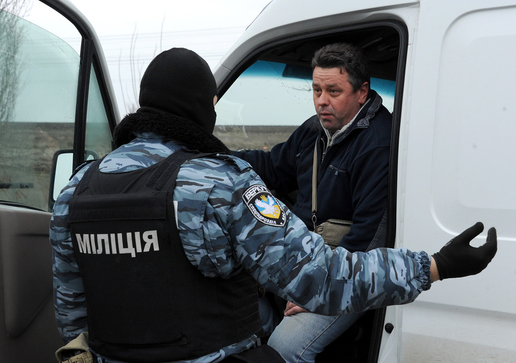 . An armed masked man wearing shoulder sleeve insignia of Ukraine\'s disbanded elite Berkut riot police force speaks with a driver at a checkpoint on a highway that connect Black Sea Crimea  peninsula to mainland Ukraine near the city of Armyansk, 150 km north of Simferopol, on February 28, 2014. AFP PHOTO / VIKTOR DRACHEV/AFP/Getty Images