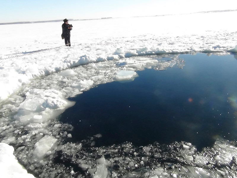 . A Russian policeman works near an ice hole, said by the Interior Ministry department for Chelyabinsk region to be the point of impact of a meteor seen earlier in the Urals region, at lake Chebarkul some 80 kilometers (50 miles) west of Chelyabinsk February 15, 2013. The meteor streaked across the sky and exploded over central Russia on Friday, sending fireballs crashing to earth which shattered windows and damaged buildings, injuring more than 500 people. REUTERS/Chelyabinsk region Interior Ministry/Handout