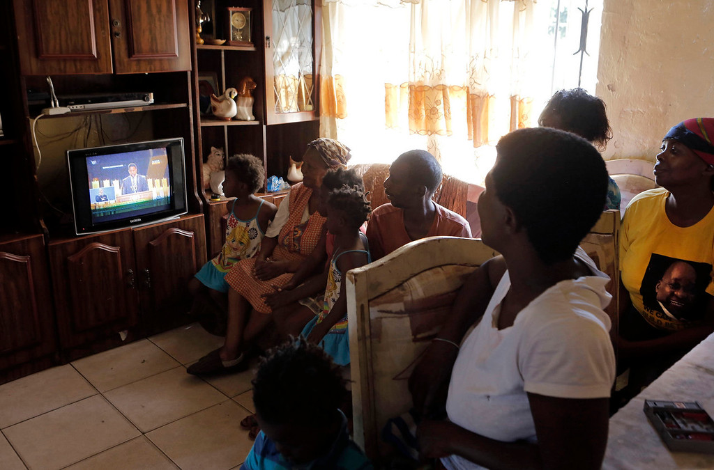 . A family watch a television showing the funeral service of former South African President Nelson Mandela at their home in the Soweto township, Johannesburg, South Africa, Sunday, Dec. 15, 2013.  (AP Photo/Markus Schreiber)