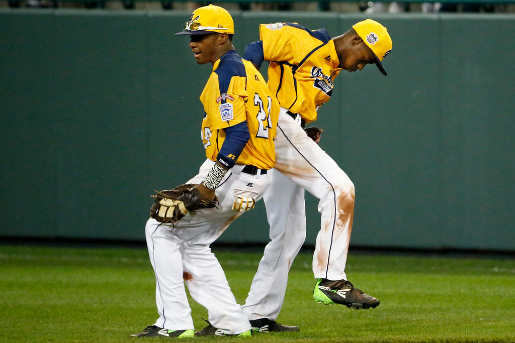 . Chicago\'s Trey Hondras, left, celebrates with Pierce Jones (23) after Jones caught the final out of a 6-5 win over Philadelphia in an elimination baseball game at the Little League World Series tournament in South Williamsport, Pa., Thursday, Aug. 21, 2014. (AP Photo/Gene J. Puskar)