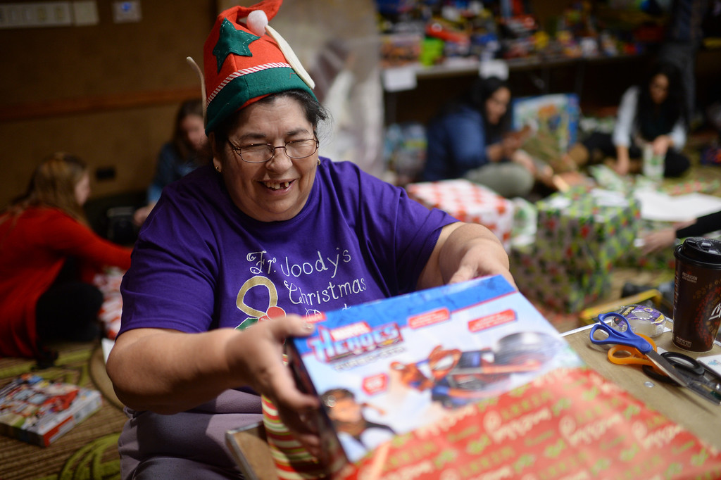 ". DENVER, CO. DECEMBER 21: Barbara Tolmich of Denver is wrapping Christmas gift during the annual Father Woody Christmas Party in Denver, Colorado December 21, 2013. In advance of handing out 5,000 gifts, volunteers are doing a ""wrapping party\"" at the Sheraton Denver Downtown Hotel. (Photo by Hyoung Chang/The Denver Post)"