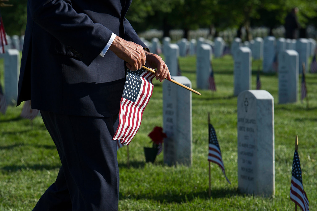 . Vice President Mike Pence walks to a gravesite to place a flag at a headstone as members of the Army 3d U.S. Infantry Regiment, The Old Guard, honor the nation\'s fallen military heroes during its annual Flags In ceremony at Arlington National Cemetery,  Thursday, May 24, 2018, in Arlington, Va. (AP Photo/Cliff Owen)