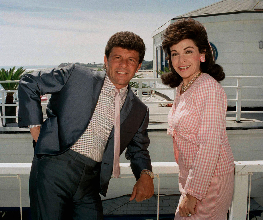 """. Frankie Avalon and Annette Funicello, who starred in \""""Beach Blanket Bingo\"""",  \""""How to Stuff a Wild Bikini\"""" and other memorable movies of the mid-Sixties, relax during break in taping of their new movie \""""Back to the Beach\"""" in Malibu, Calif., April 13, 1987. They play onetime beach lovers who move to Ohio. (AP Photo/Bob Galbraith)"""