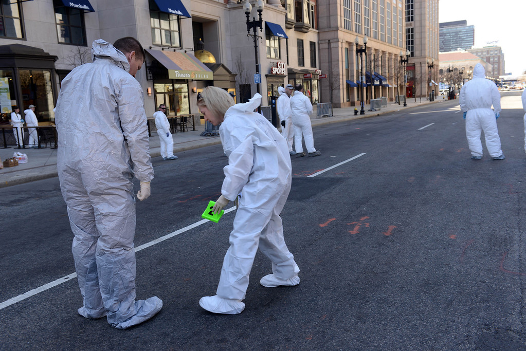 . An FBI crime scene investigator places an evidence marker on Boylston Street just past Berkeley Street near the scene of the Boston Marathon bombing April 17, 2013 in Boston, Massachusetts.  Investigators continue to work the scene of two bomb explosions at the finish line of the marathon that killed 3 people and injured over one hundred more. (Photo by Darren McCollester/Getty Images)