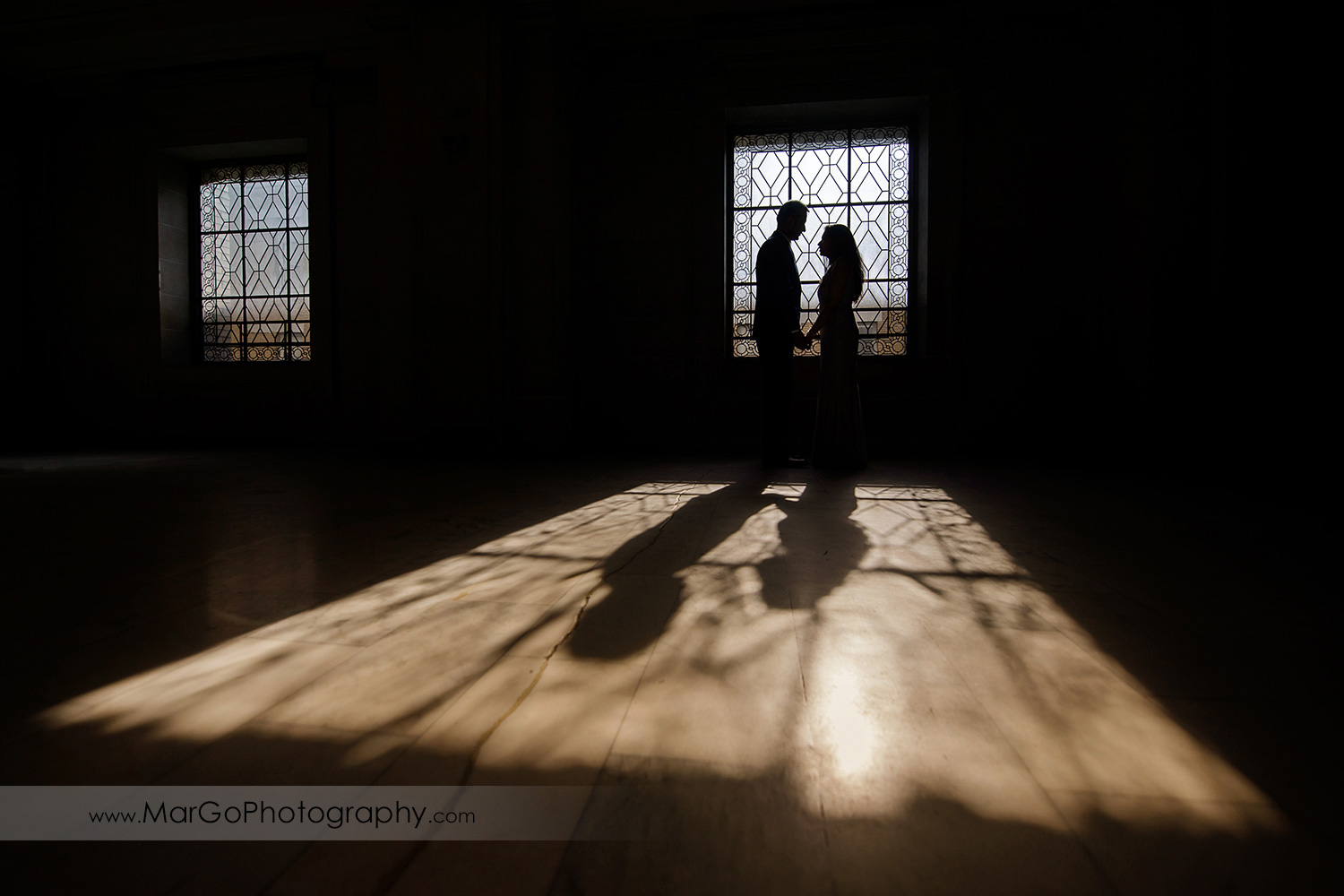 silhouette of the couple looking at each other in front of the window on the third floor of San Francisco City Hall