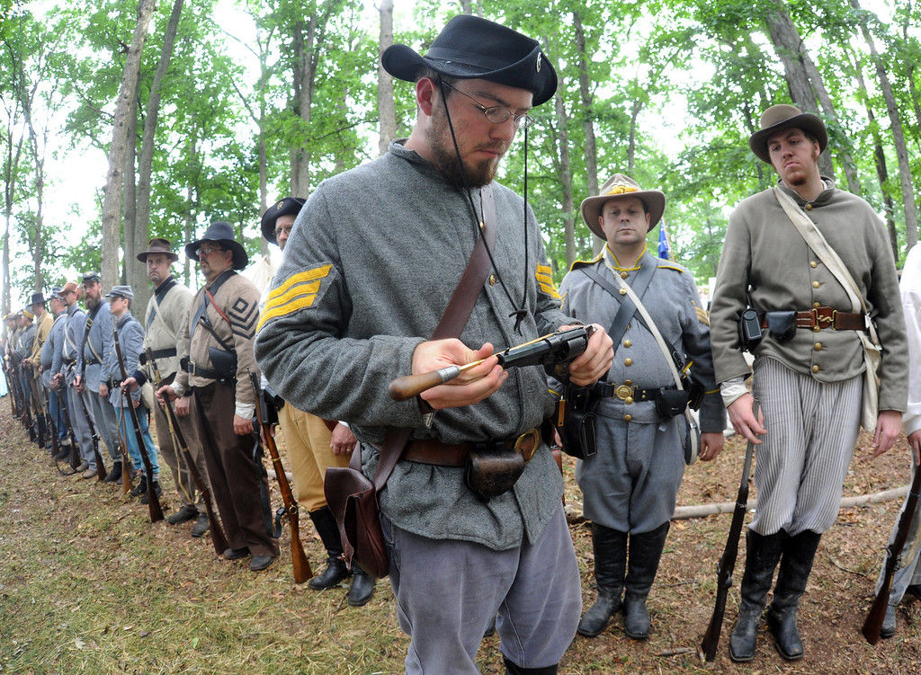 . James Stanton, portraying a sergeant in the 6th Cavalry out of Missouri, inspects the weapons of the platoon in the Confederate army\'s encampment in Gettysburg, Pa., for the 150th celebration of the Battle of Gettysburg on Thursday, June 27, 2013. (AP Photo/York Daily Record, Jason Plotkin)