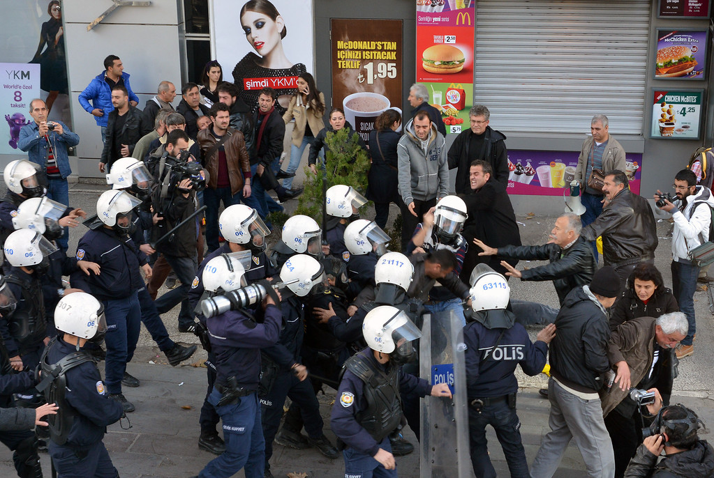 . A man tries to stop police officers as riot police prepares to use pepper gas to disperse thousands of Turkish teachers who were gathered to protest against the government\'s education and economic policies in Ankara, Turkey, Saturday, Nov. 23, 2013.(AP Photo)