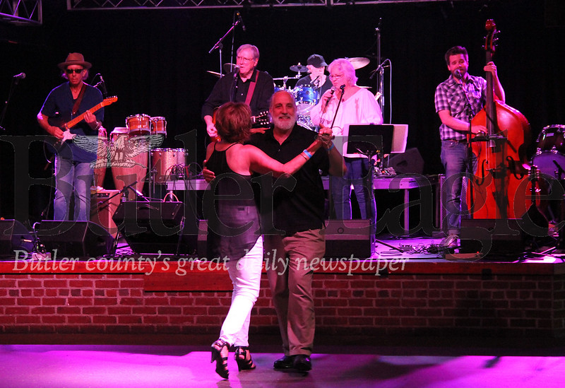 Linda Kotzbauer and Carl Johnson dance along to Dennis McCurdy, a local lawyer, playing with his band Lonesome No More on Sunday at Jergel's Rhythm Grille night during a fundraiser for flood victims.