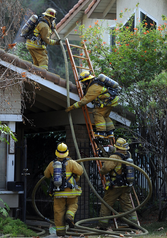 . Los Angeles County Firefighters climb a ladder to battle a fire that damaged a single family home. The fire started in the garage along the 1300 block of Via Verde. No injuries, but 5 cars were destroyed including two jaguars in San Dimas, Calif., on Saturday, Jan.4, 2014. 