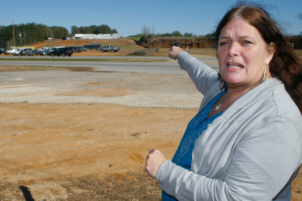 Description of . Ronda Wilbur, a neighbor of murder suspect Jimmy Lee Dykes, points as she speaks with the media about encounters she's had with him at the scene of a shooting and hostage taking in Midland City, Alabama, January 31, 2013. A gunman suspected of fatally shooting an Alabama school bus driver before holing up in an underground bunker with a young child is a Vietnam veteran with anti-government views, authorities and an organization that tracks hate groups said. REUTERS/Phil Sears