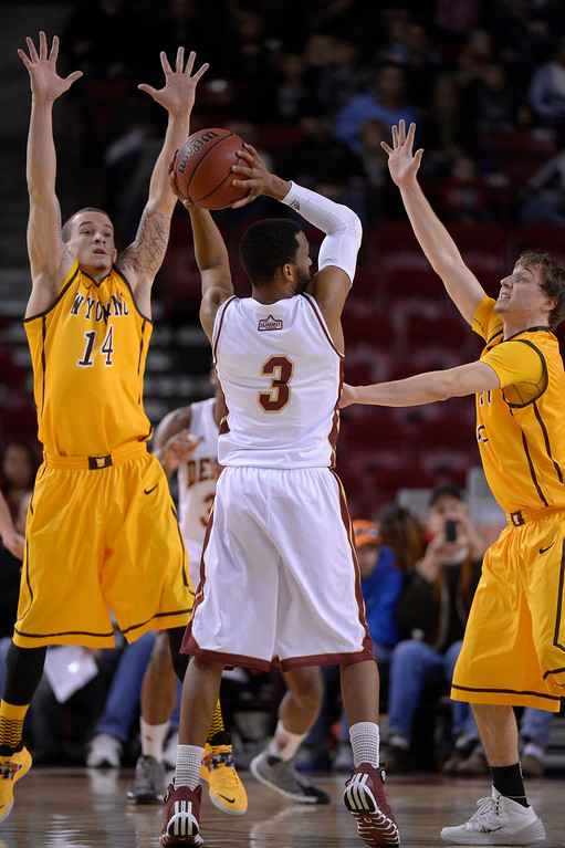 . Denver Pioneers guard Jalen Love (3) gets double teamed by Wyoming Cowboys guard Josh Adams (14) and Wyoming Cowboys guard Riley Grabau (2) during the first half December 15, 2013 Magness Arena. (Photo by John Leyba/The Denver Post)