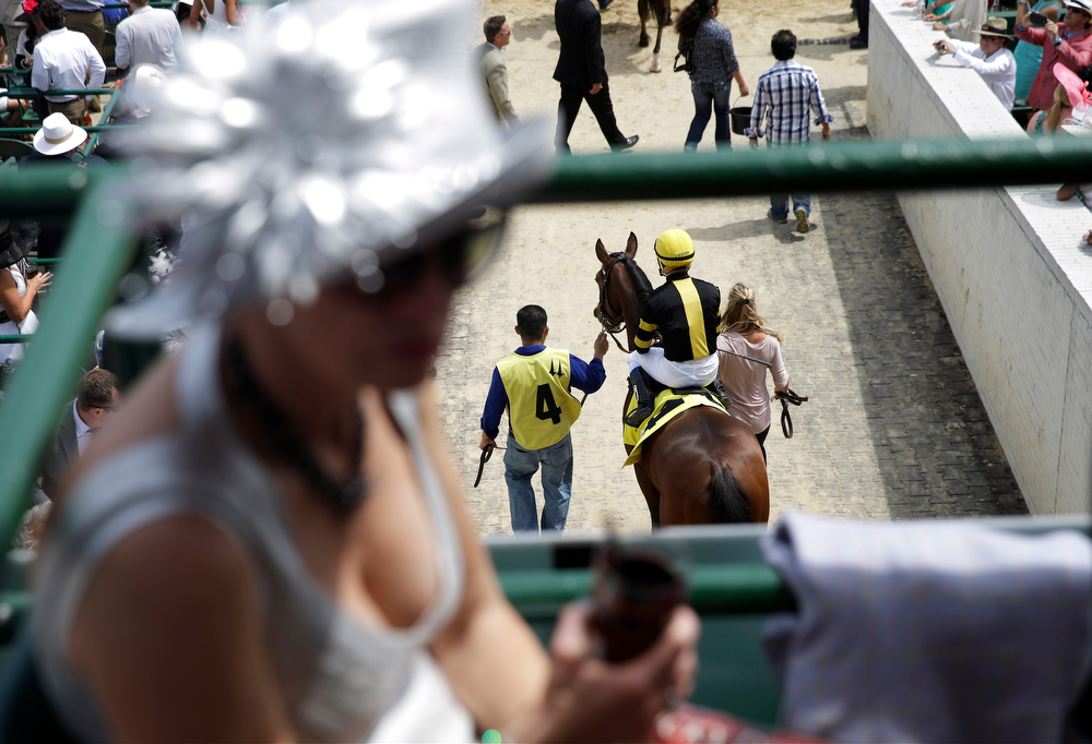 Description of . A race horse is lead out to the track for a race before the 140th running of the Kentucky Derby horse race at Churchill Downs Saturday, May 3, 2014, in Louisville, Ky. (AP Photo/David Goldman)