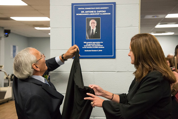 10/03/19 Wesley Bunnell | StaffrrCCSU officially opened the Dr. Antone B. Capitao Biomechanics Laboratory Classroom with a ribbon cutting on Thursday October 3, 2019. Dr. Capitao helps to unveil the dedication plaque in his honor with the help of Dr. KImberly Kostelis Dean of the School of Education & Professional Studies.