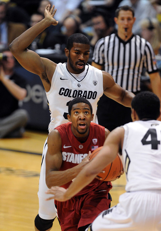 . Stanford\'s Chasson Randle, center, drives past Colorado\'s Jeremy Adams during the first half of an NCAA college basketball game on Thursday, Jan. 24, 2013, in Boulder, Colo. (AP Photo/Daily Camera, Cliff Grassmick)