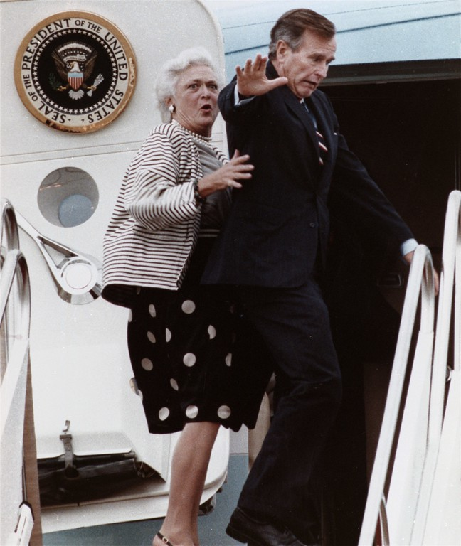 . First lady Barbara Bush reacts after President Bush accidentally stepped on her toe while boarding Air Force One at Andrews Air Force Base, Md. Friday, Sept. 22, 1989 for a flight to New Jersey. (AP Photo/Charles Tasnadi)