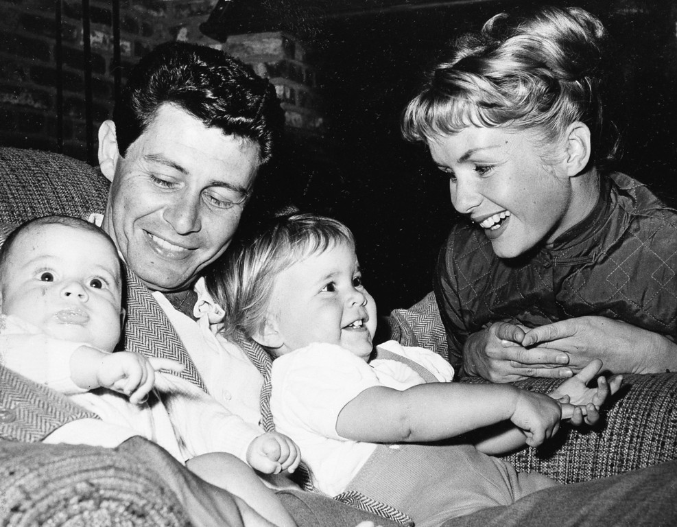 . Singer Eddie Fisher, out of the hospital in time for Father\'s Day, cuddles his two youngsters four-month old Todd, left, and 19-month-old Carrie.  Looking on is their equally famous mother, actress Debbie Reynolds.   (AP Photo)