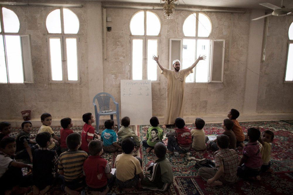 Description of . Syrian teacher Abu al-Fattah gestures while delivering a lesson at an improvised school in the town of Azaz, on the border with Turkey, on September 17, 2012. Over 2,000 Syrian schools have been damaged or destroyed and hundreds more are being used as shelters, the UN said on September 14, warning it faced a staggering challenge for the new school year. MARCO LONGARI/AFP/Getty Images