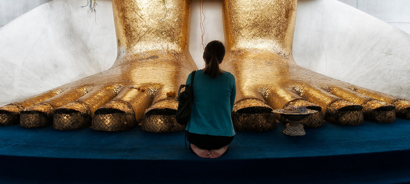 Woman prayer in front of a giant statue of Buddha.   Bangkok, Thailand, 2012.