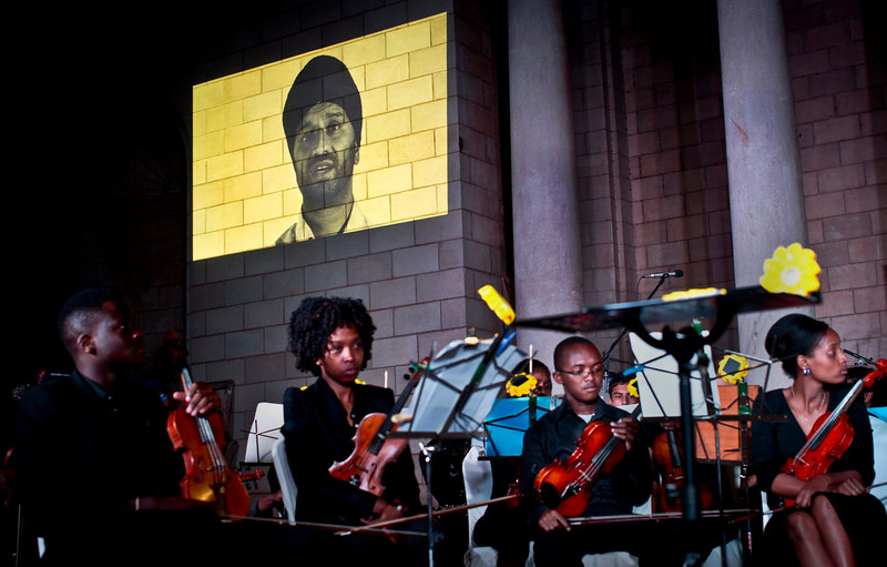 . Members of the Westgate Memorial Service Orchestra listen in silence as a video testimony of survivor Ambi Ghataurhae, who lost his son and mother in the Westgate Mall attack, is projected on the wall during a concert of remembrance for the victims of the attack, which coincides with the International Day of Peace, at the Nairobi National Museum in Kenya Sunday, Sept. 21, 2014. Relatives of the dead, survivors and shop owners converged outside Nairobi\'s Westgate Mall and the Amani Garden memorial site in the Karura Forest on the edge of the city on Sunday, lighting candles and laying flowers in memory of those killed a year ago when gunmen stormed the upscale mall. (AP Photo/Ben Curtis)