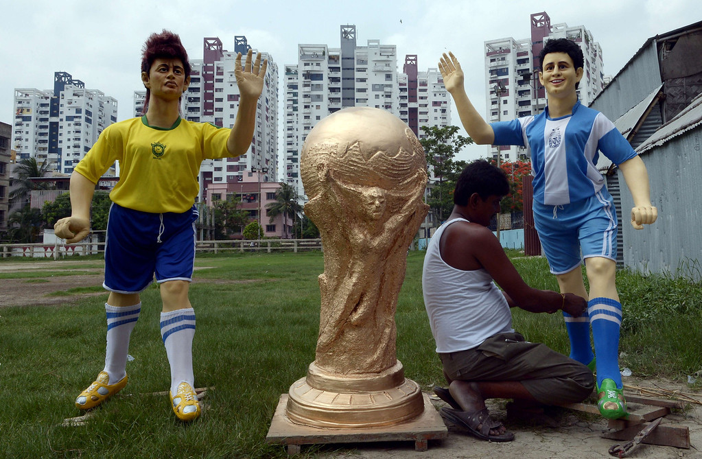 . An Indian artist gives finishing touches to a clay idol of Argentine soccer player Lionel Messi (R) alongside a clay idol of Brazilian soccer player Neymar and a replica of FIFA World Cup for a football club, outside the workshop in Kolkata on June 10, 2014.   Football fans in the eastern Indian city are gearing up for the upcoming Brazil FIFA World Cup 2014 and decorating their clubs with football-related paraphernalia.  AFP PHOTO/ Dibyangshu SARKAR/AFP/Getty Images