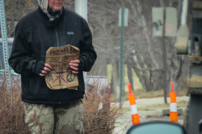 A man walks along a Kansas City street in Feb. 2021 with a sight stating he is homeless.