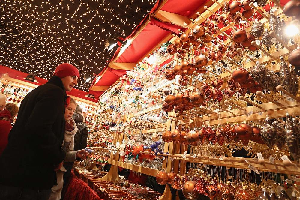 Description of . Visitors look at Christmas decorations for sale at the Kaethe Wohlfahrt stand at the annual Christmas market at Gendarmenmarkt on its opening day on November 26, 2012 in Berlin, Germany. Christmas markets, with their stalls selling mulled wine, Christmas tree decorations and other delights, are an integral part of German Christmas tradition, and many of them opened across Germany today.  (Photo by Sean Gallup/Getty Images)