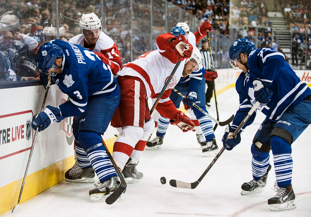 . Detroit Red Wings\' Johan Franzen, center, loses the puck to Toronto Maple Leafs\' Mike Santorelli, right, during first-period preseason NHL hockey game action in Toronto, Friday, Oct. 3, 2014. (AP Photo/The Canadian Press, Aaron Vincent Elkaim)