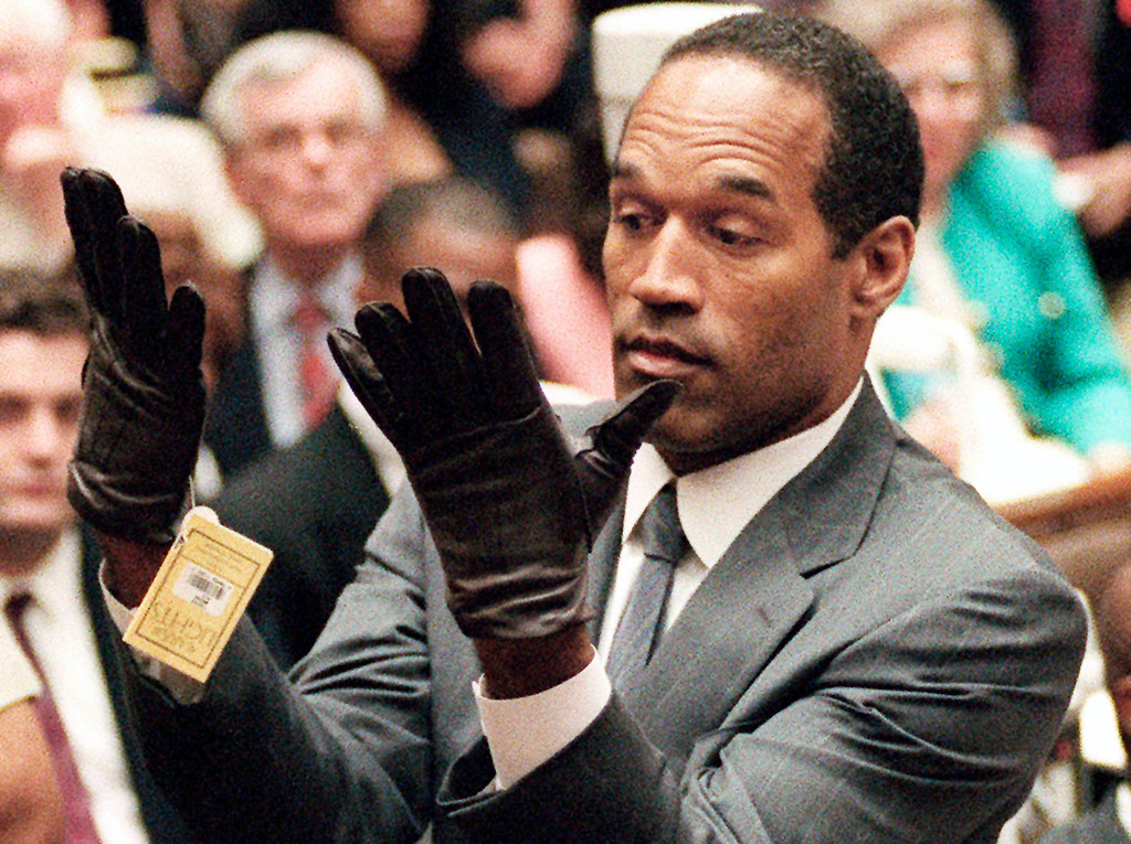 . FILE - In this June 21, 1995, file photo, O.J. Simpson holds up his hands before the jury after putting on a new pair of gloves similar to the infamous bloody gloves during his double-murder trial in Los Angeles.  (AP Photo/Vince Bucci, Pool, File)